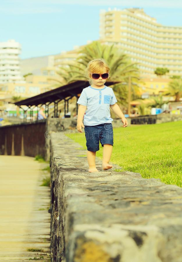 Cute fashionable baby boy in sunglasses. With blond hair in blue tshirt and shorts walks barefoot on stone wall on sunny summer day on natural background royalty free stock images
