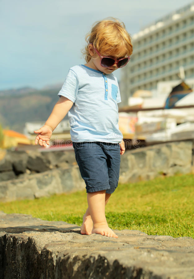 Cute fashionable baby boy in sunglasses. With blond hair in blue tshirt and shorts walks barefoot on stone wall on sunny summer day on natural background stock photo
