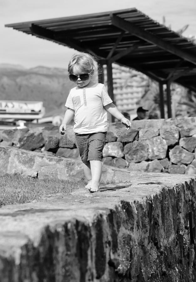 Cute fashionable baby boy in sunglasses. With blond hair in blue tshirt and shorts walks barefoot on stone wall on sunny summer day on natural background royalty free stock photos
