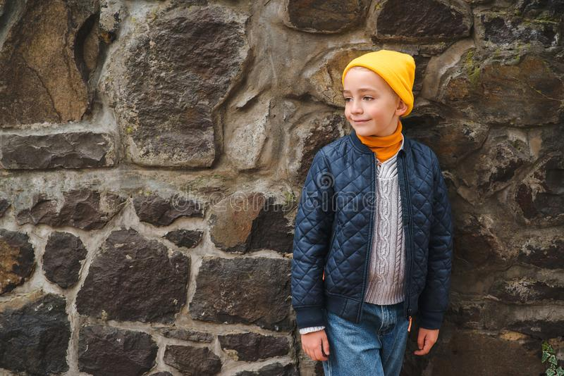 Cute fashionable boy in jacket and yellow hat, outdoors. Handsome boy at walk. Kids fashion. Happy stylish boy posing near stone royalty free stock photos