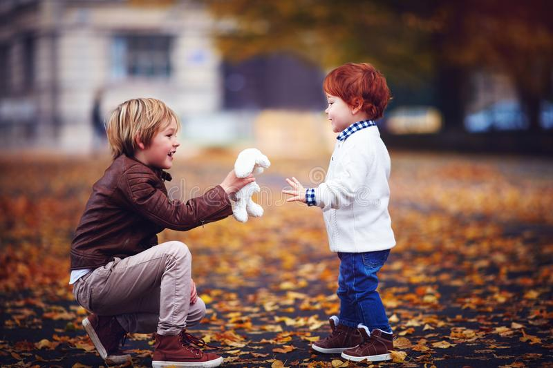 Cute fashionable brothers, kids, boys playing together in autumn park royalty free stock images