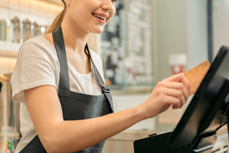 Cute female cashier holding credit card near monitor royalty free stock image