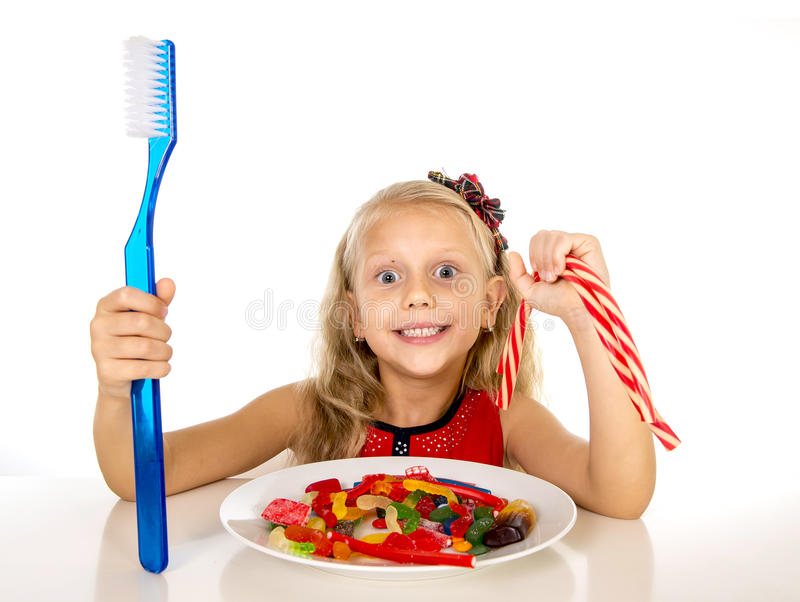 Cute female child eating dish full of sweets and holding huge toothbrush in dental care and health concept. And unhealthy sugar abuse isolated on white stock images