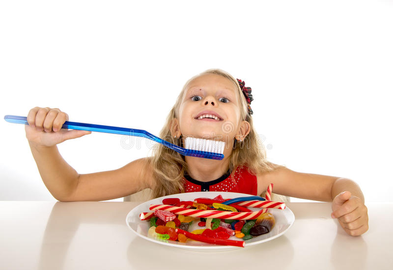 Cute female child eating dish full of sweets and holding huge toothbrush in dental care and health concept. And unhealthy sugar abuse isolated on white royalty free stock photo