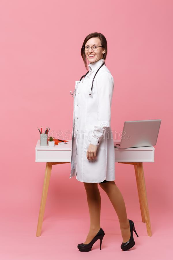 Cute female doctor stand in front of desk with pc computer, medical document in hospital isolated on pastel pink wall stock photo