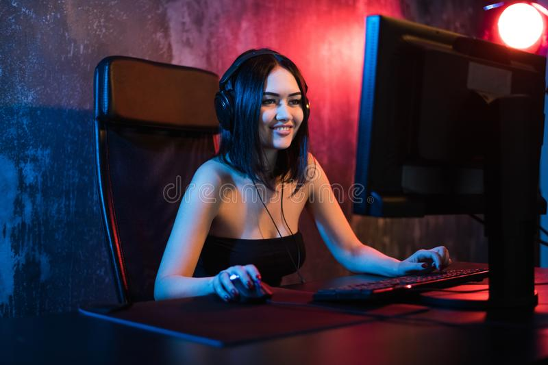 A cute female gamer girl sits in a cozy room behind a computer and plays games. Woman live streaming computer video. Games to her fans. Streamer and gamer stock photos