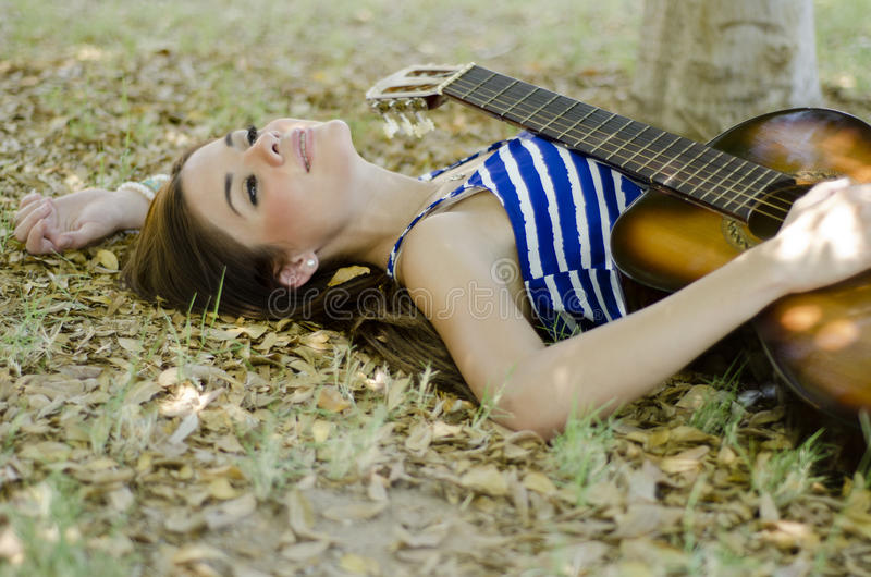 Cute female musician at the park. Beautiful female musician relaxing at the park and holding a guitar royalty free stock photography