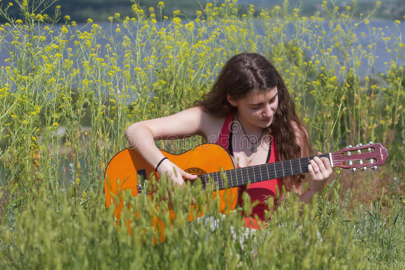 Cute female Musician sitting on green Grass. Meadow with Spring yellow Flowers playing on Guitar outdoors royalty free stock images