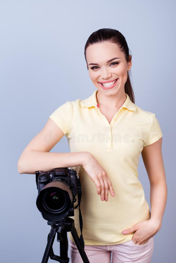 Cute female photographer with beaming smile is standing near the stock image