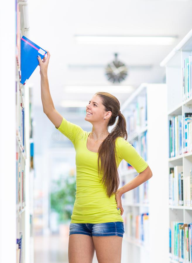 Cute female university/highschool student in library stock image