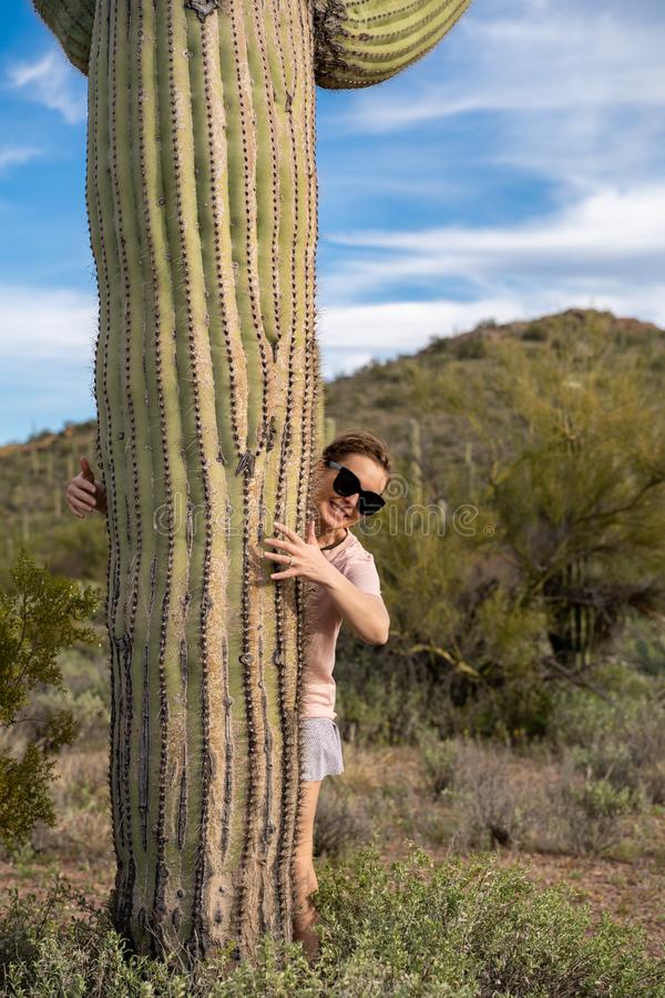 Cute female woman stands next to a large Saguaro cactus in the Sonoran desert, giving it a hug with her arms.  royalty free stock photo