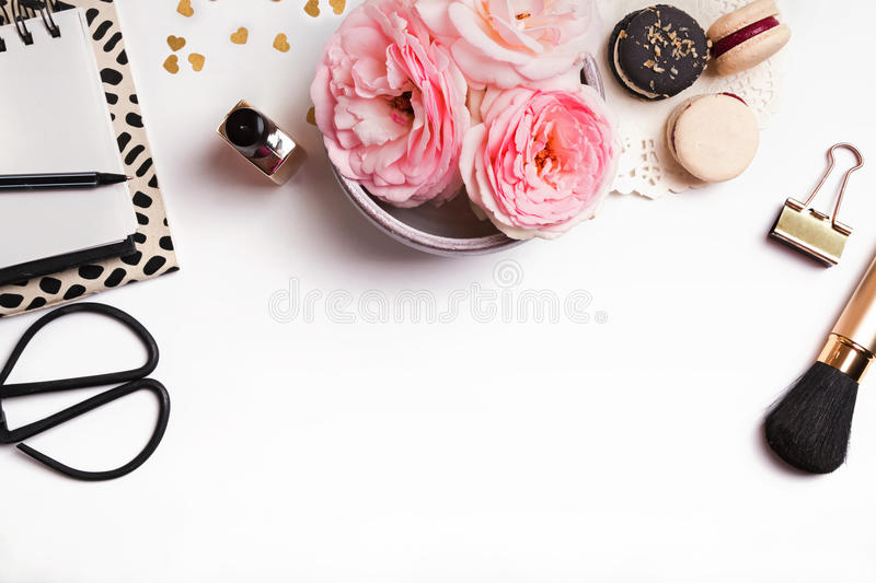 Cute feminine stuff on white background, top view. Beautiful pink flowers, french macarons, notepad and other cute feminine stuff on white background, top view royalty free stock photography