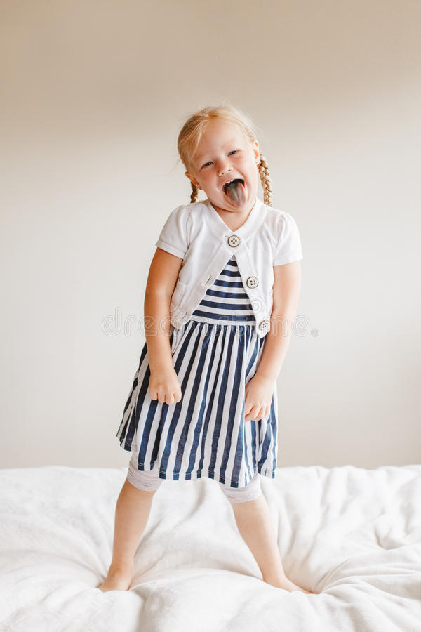 Cute finny white Caucasian blonde girl jumping on bed at home. Portrait of cute finny white Caucasian blonde girl jumping on bed at home and showing tongue stock image