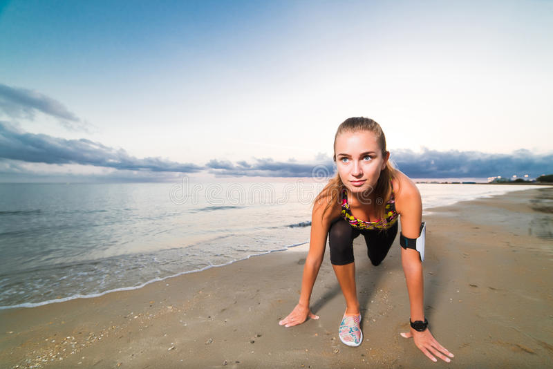 Cute fit girl starts running on beach at sunrise royalty free stock image