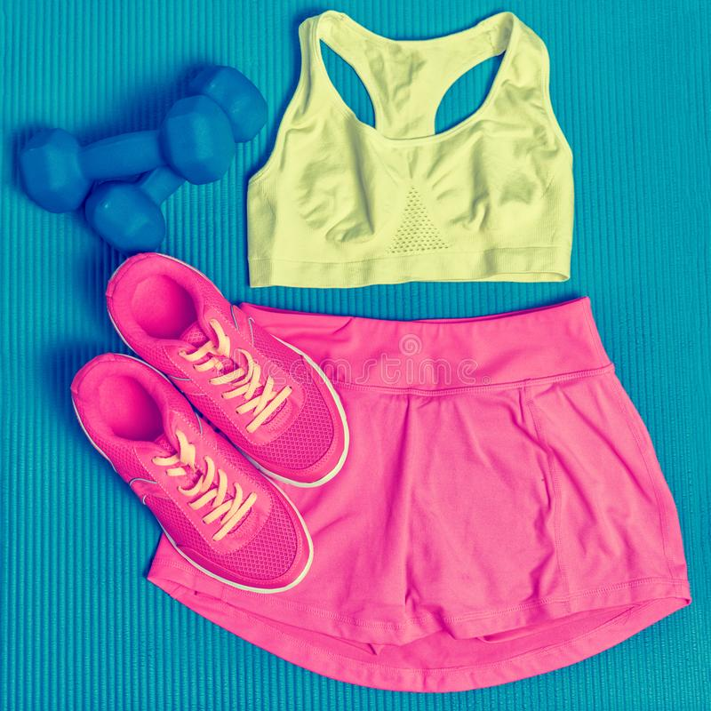 Cute fitness clothing -Sports bra and skort skirt fashion outfit to wear at the gym. Clothes layed on exercise mat with dumbbells royalty free stock image