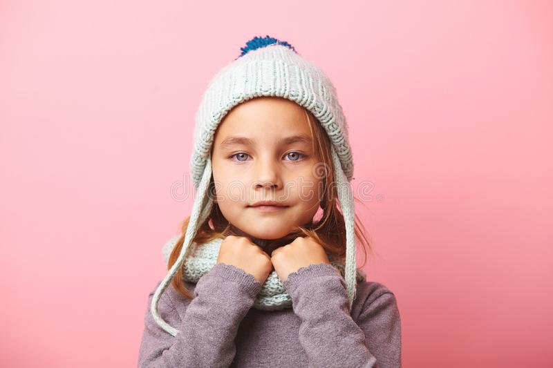 Cute five years little girl on pink background, wears beautiful winter hat and scarf. stock photos