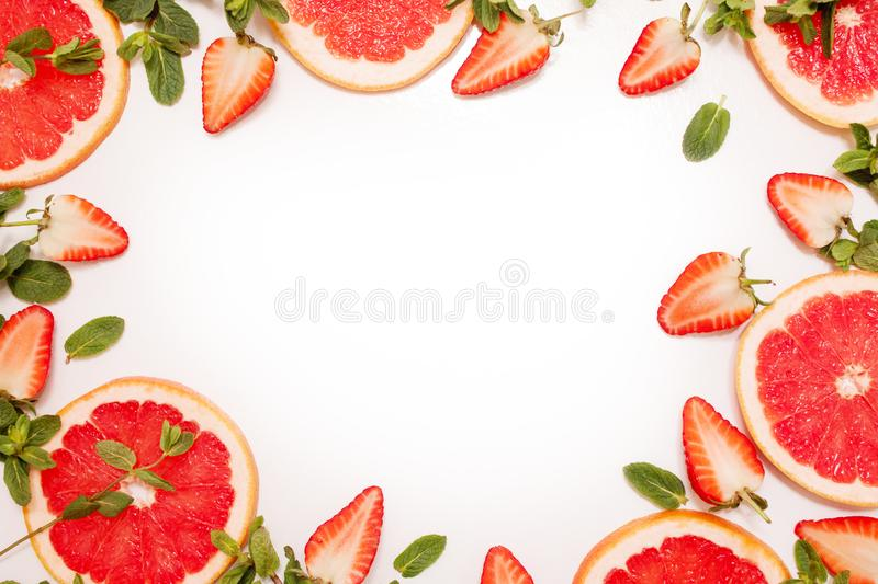 Cute flat lay with fresh fruit, sliced strawberry and grapefruit or red orange, mint leaves on white background. royalty free stock photography