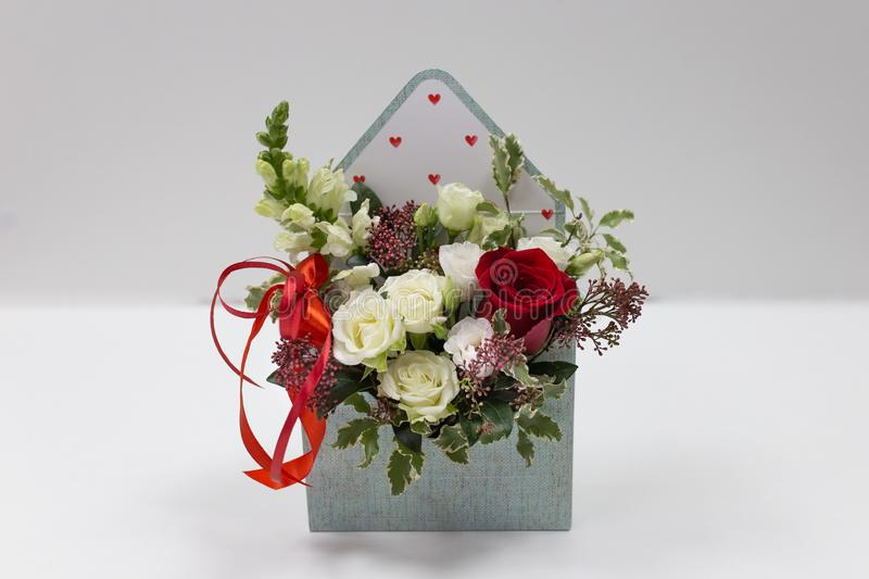 Cute floral arrangement gift of fresh flowers in a box in the form of an envelope on a light background. Flowers: roses, snapdragon, leaves. Primary colors stock image