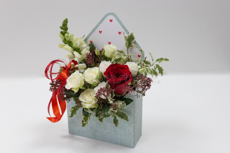 Cute floral arrangement gift of fresh flowers in a box in the form of an envelope on a light background. Flowers: roses, snapdragon, leaves. Primary colors royalty free stock photography