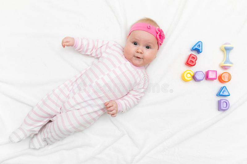 Cute four month old baby wrapped into towels after shower in bed at home stock photos