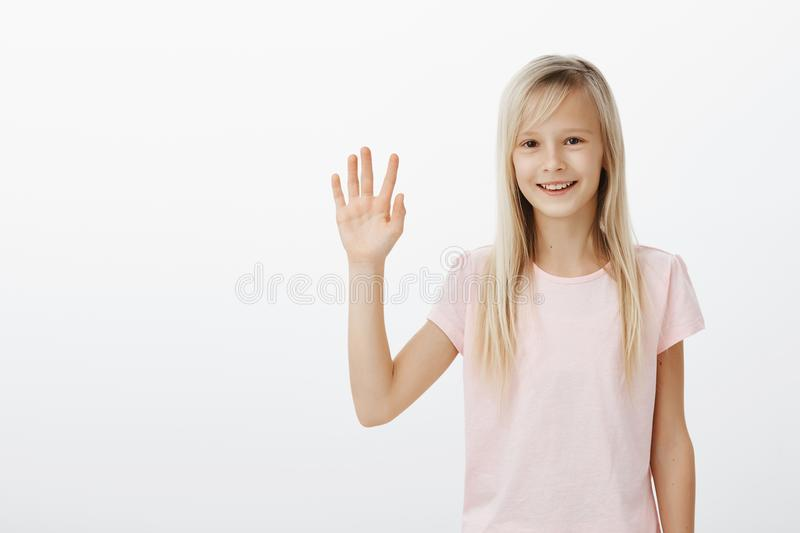 Cute friendly girl meeting new classmates, saying hi and hoping get along. Positive happy female child with blond hair stock photos