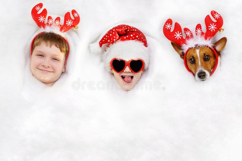 Cute friends suit in a reindeer and Santa hat lying in snow. Cute kids and dog in a reindeer and Santa hat lying in snow background. Christmas, new year holiday royalty free stock photo