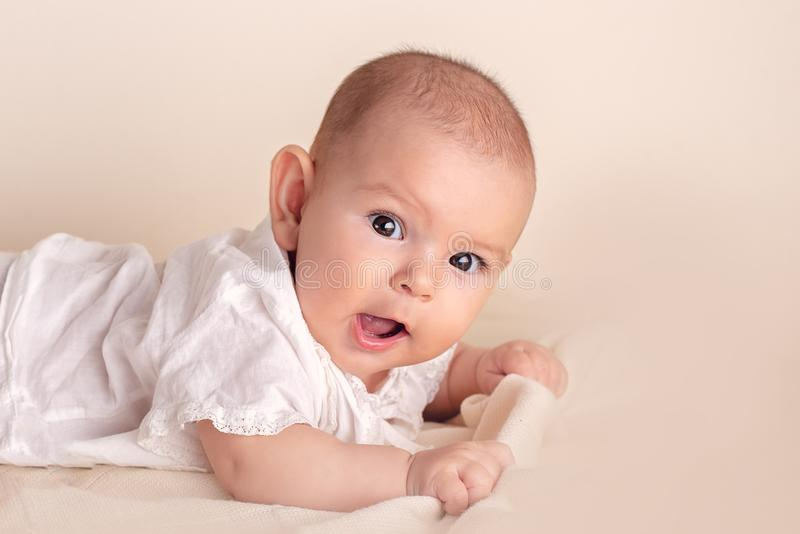 Cute funny baby with big beautiful eyes lying on a white blanket royalty free stock photography