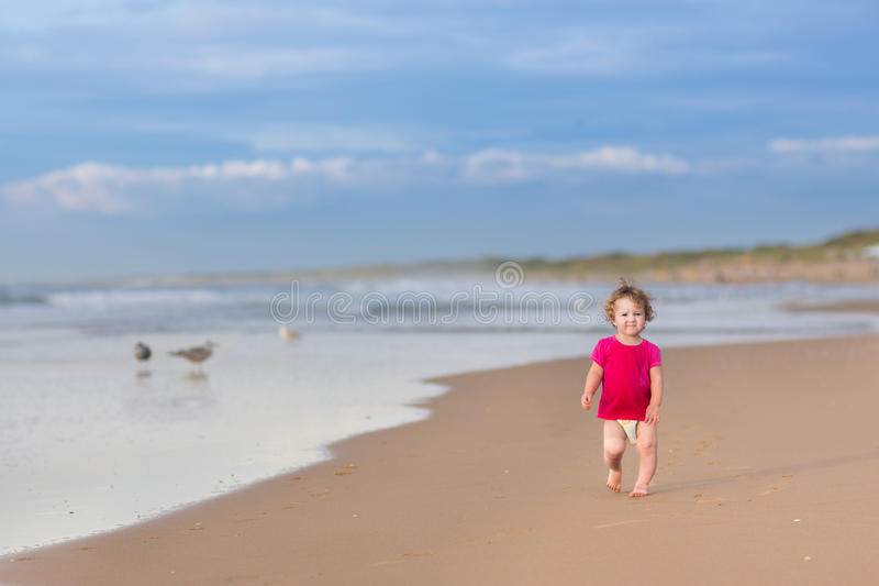 Cute funny baby girl running on beautiful beach stock photography