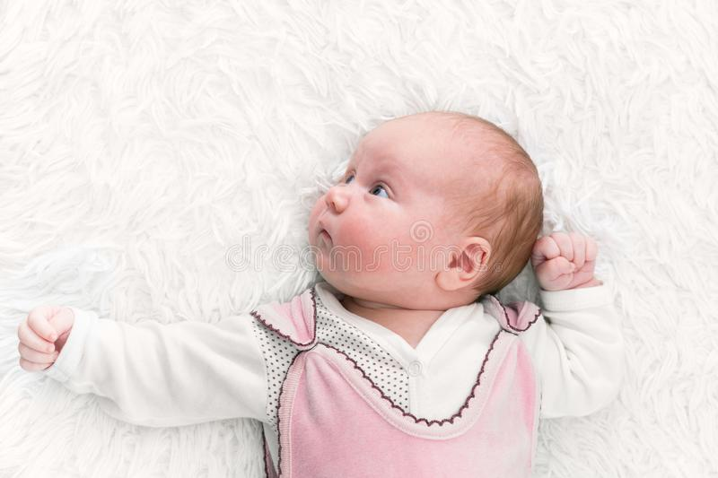 Cute funny baby 1 month old wearing pink suit lying in bed. Looking away. royalty free stock image