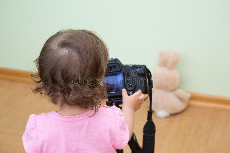 Cute funny beautiful baby in a pink T-shirt photographs her bunny. The baby stands and holds a DSLR camera on a tripod against the. Cute funny beautiful baby in stock image