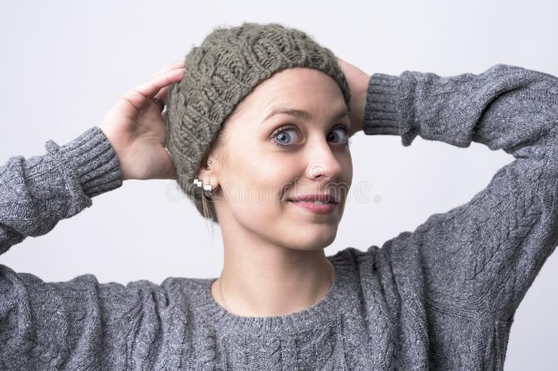 Cute funny blue eyes young woman trying on gray knitted cap stock images