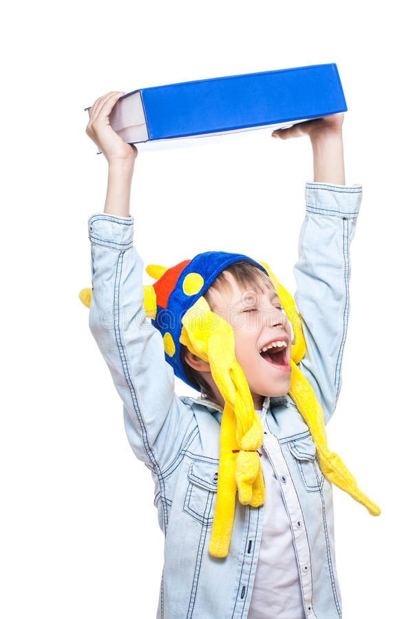 Cute funny boy in a blue shirt holding a very big blue book. Cute angry blond boy in holding a very big blue book above wanting to throw it as a way of protest ( royalty free stock photos