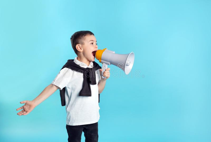 Cute funny boy with megaphone on color background. Space for text royalty free stock photos