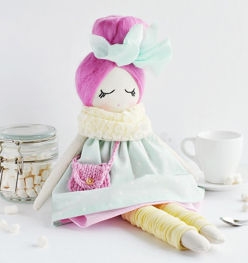 Cute fabric doll with pink hair. Cute and funny fabric doll with pink topknot hairstyle stock photography