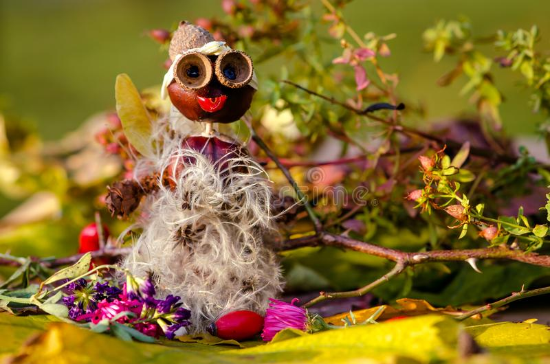 Autumn. Cute funny figures made from autumn fruits, chestnut and acorns posing outdoors in nature royalty free stock photography
