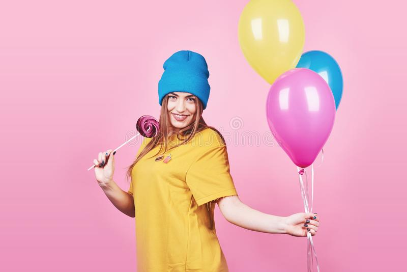 Cute funny girl in blue cap portrait holds an air colorful balloons and lollipop smiling on pink background. Beautiful stock photo