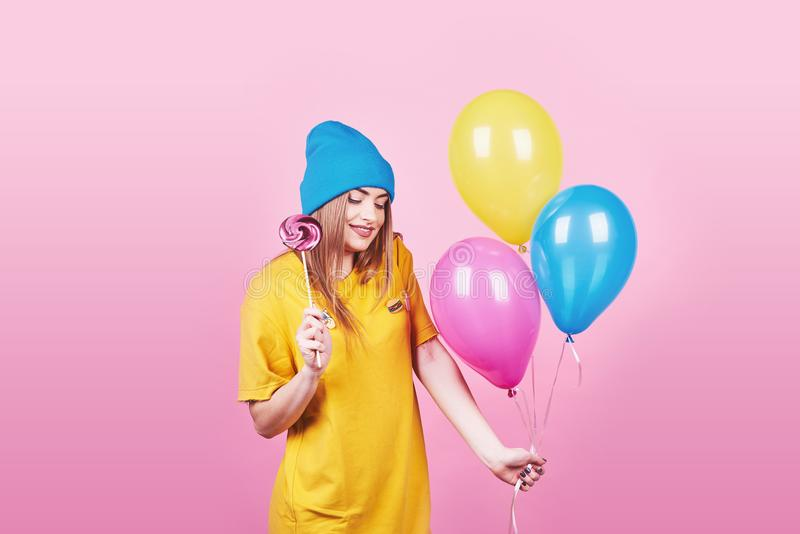 Cute funny girl in blue cap portrait holds an air colorful balloons and lollipop smiling on pink background. Beautiful royalty free stock image
