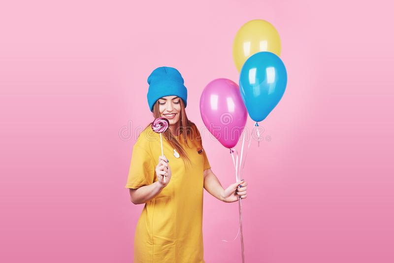 Cute funny girl in blue cap portrait holds an air colorful balloons and lollipop smiling on pink background. Beautiful royalty free stock images