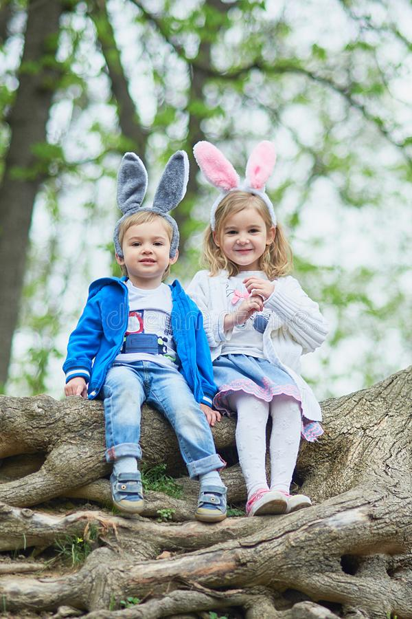 Cute funny girl and boy with Easter eggs at park. easter concept. Children playing with easter eggs on Easter day. Family holiday royalty free stock photography
