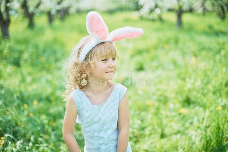 Cute funny girl with Easter eggs and bunny ears at garden. easter concept. Laughing child at Easter egg hunt. Child in park baby caucasian celebrate royalty free stock photography
