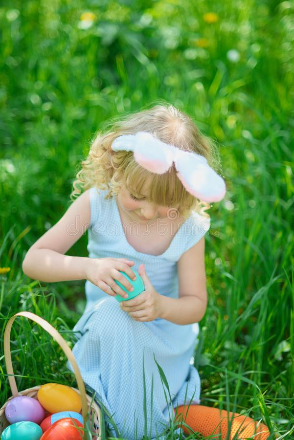 Cute funny girl with Easter eggs and bunny ears at garden. easter concept. Laughing child at Easter egg hunt. Child in park with basket full of eggs, spring royalty free stock photo