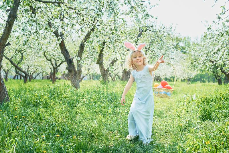 Cute funny girl with Easter eggs and bunny ears at garden. easter concept. Laughing child at Easter egg hunt. Child in park with basket full of eggs, spring royalty free stock photography