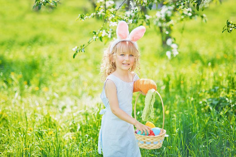Cute funny girl with Easter eggs and bunny ears at garden. easter concept. Laughing child at Easter egg hunt. Child in park with basket full of eggs, spring stock photography