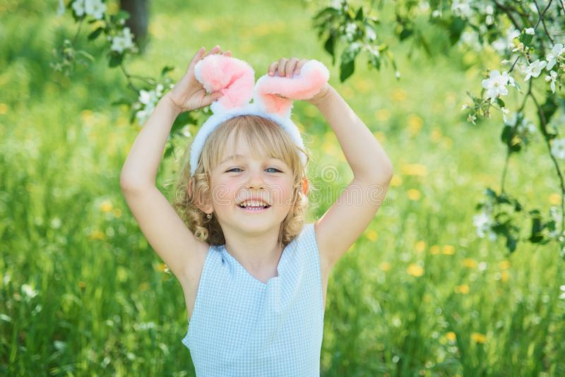 Cute funny girl with Easter eggs and bunny ears at garden. easter concept. Laughing child at Easter egg hunt. Child in park with eggs, spring concept baby royalty free stock image