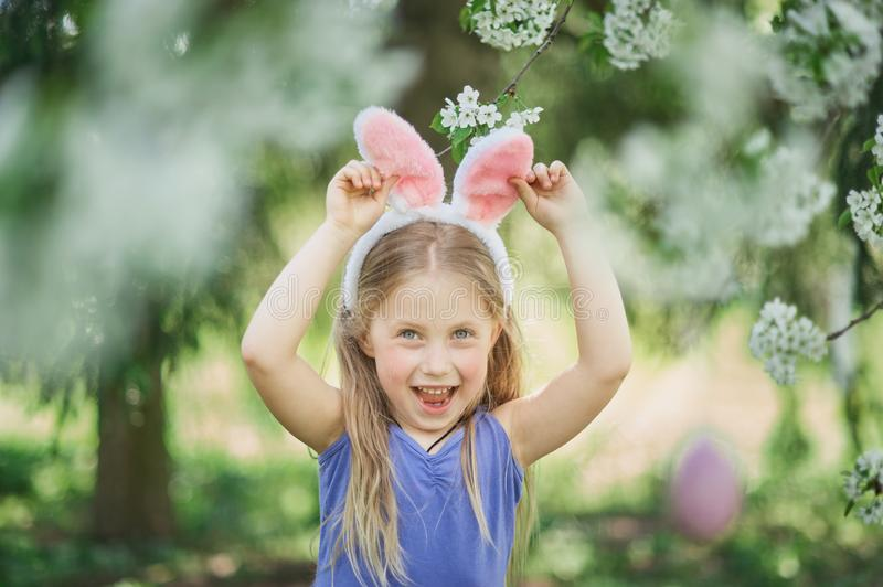 Cute funny girl with Easter eggs and bunny ears at garden. easter concept. Laughing child at Easter egg hunt. Baby caucasian celebrate celebration cheerful stock photo