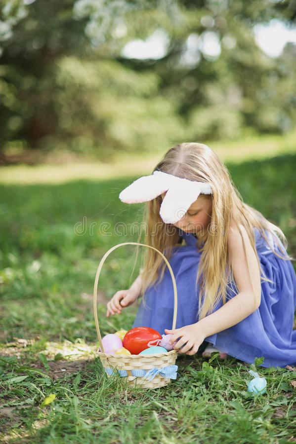 Cute funny girl with Easter eggs and bunny ears at garden. easter concept. Laughing child at Easter egg hunt. Baby caucasian celebrate celebration cheerful royalty free stock photos