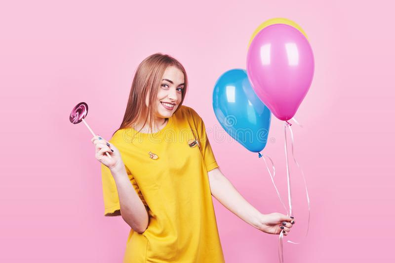 Cute funny girl portrait holds an air colorful balloons and lollipop smiling on pink background. Beautiful multicultural royalty free stock photo