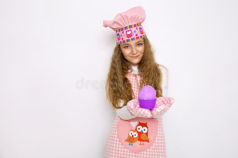 Cute funny girl with slime in the kitchen. The girl cooks and bakes her muffins, makes a cake and slime. stock photo