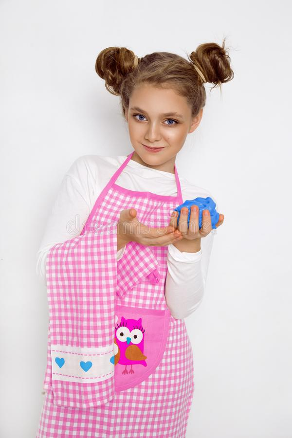Cute funny girl with slime in the kitchen. The girl cooks and bakes her muffins, makes a cake and slime. royalty free stock image