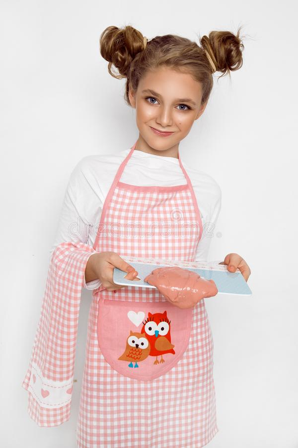 Cute funny girl with slime in the kitchen. The girl cooks and bakes her muffins, makes a cake and slime. royalty free stock photo